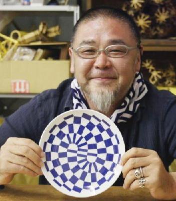 2020年東京五輪・パラリンピックのエンブレム「組市松紋」の図柄をアレンジした有田焼の皿を手にするエンブレム制作者の野老朝雄氏(大会組織委員会提供)